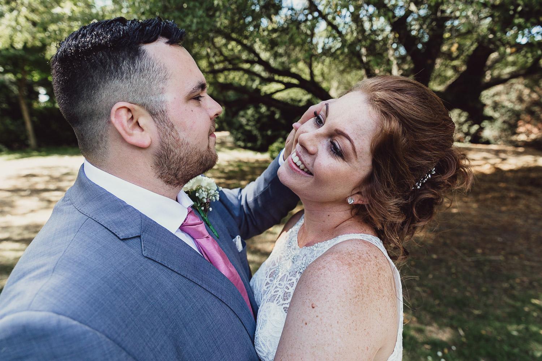 Norfolk norwich  wedding bride and groom walking in garden stroking hair