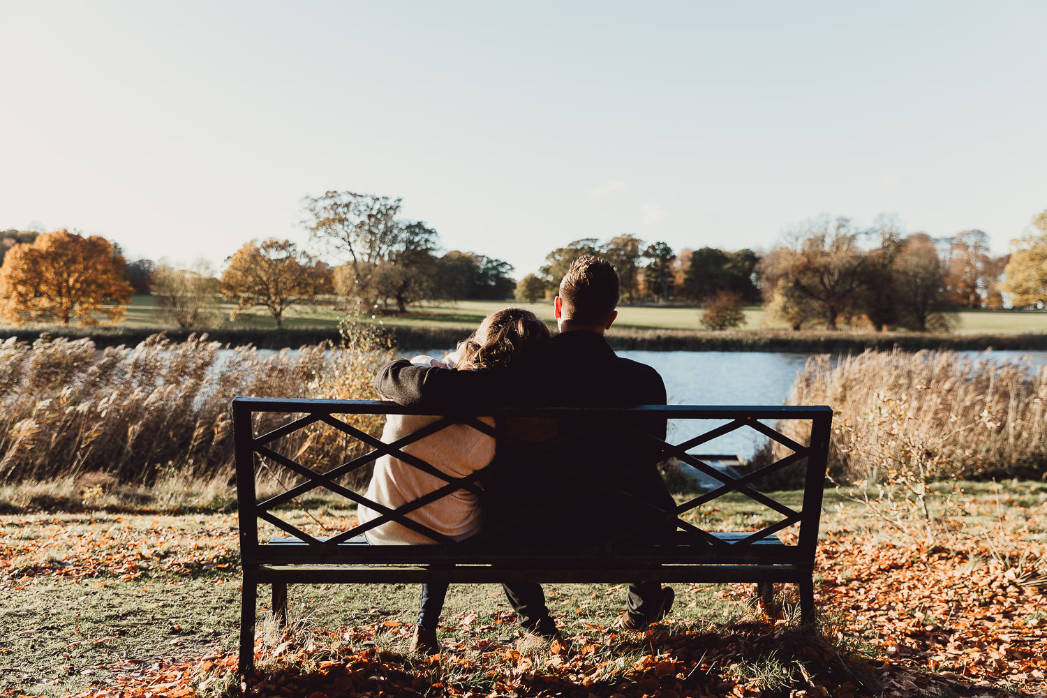 Engagement shoot Norfolk golden hour autumn sitting on a bench