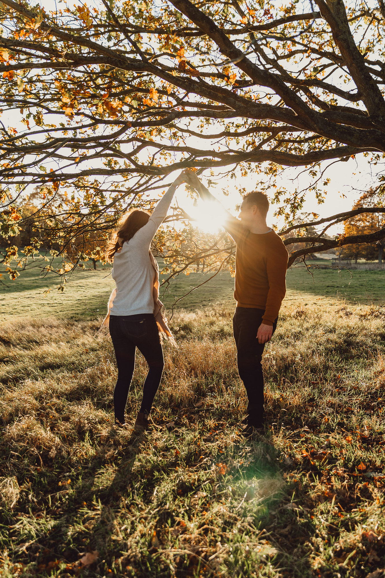 Engagement shoot Norfolk golden hour autumn dancing under an autumnal tree at sunset