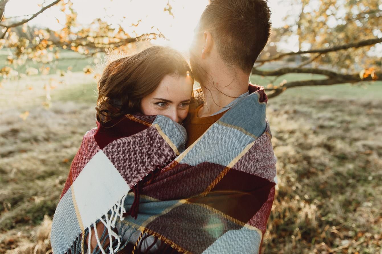 Engagement shoot Norfolk golden hour autumn wrapped in blanket at sunset