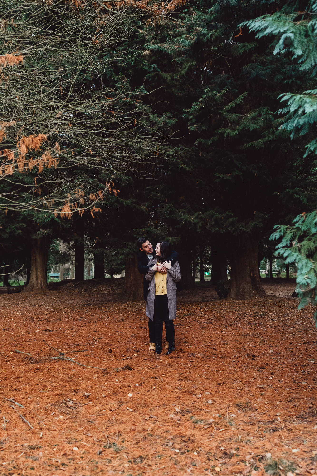Engagement shoot  autumn woodland Norfolk cuddling under tree